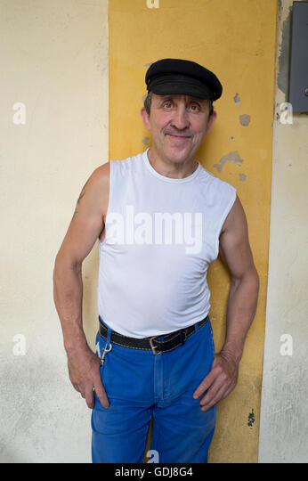 Arles, France. A typical traditional French workman wearing blue trousers, sleevless t shirt and a flat cap. - Stock Image