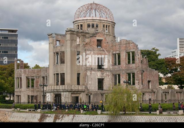 Genbaku Dome (Atomic Bomb Dome) with students in foreground, Hiroshima Peace Memorial Park, Hiroshima, Japan. - Stock Image