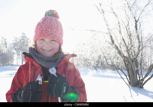 Portrait of happy girl in warm clothing - Stock Image