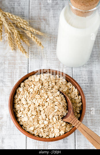 Organic oat flakes, rolled oats in brown ceramic bowl, wheat ears and bottle of milk on rustic white table. Vertical - Stock Image