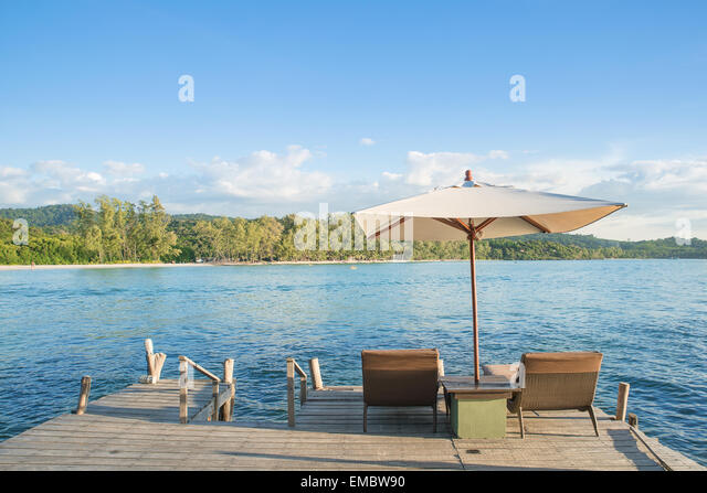 Summer, Travel, Vacation and Holiday concept - Beach chairs and umbrella on wooden desk against blue sky in Phuket,Thailand - Stock-Bilder