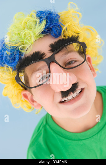 Young boy wearing clown wig and fake nose - Stock Image