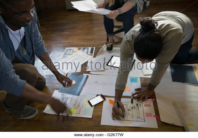 Designers reviewing plans and paperwork on office floor - Stock Image