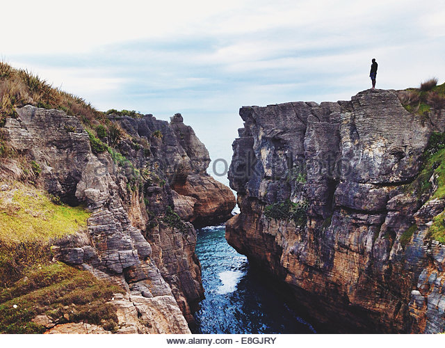 New Zealand, Silhouette of person standing on cliff - Stock Image