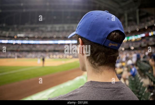 A lone Milwaukee Brewers baseball fan surveys the field between innings. - Stock Image