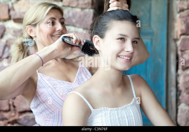 Mother brushing daughter's hair - Stock Image