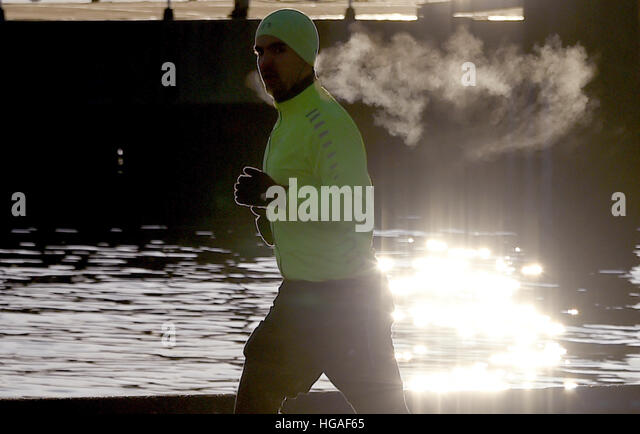 Kiel, Germany. 06th Jan, 2017. A jogger runs along the Foerde river shortly after sunrise in Kiel, Germany, 06 January - Stock Image