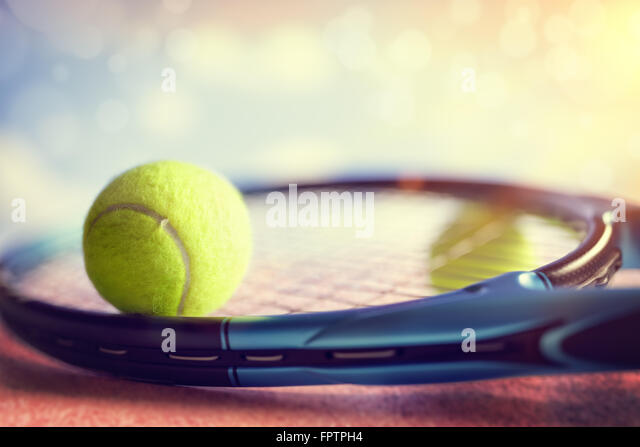 Tennis ball resting on top of a tennis racket on a red asphalt court - Stock Image
