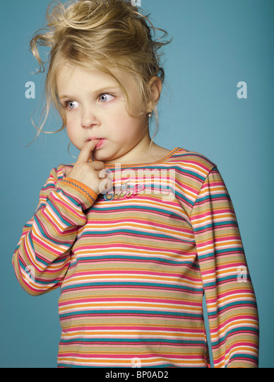Portrait of little girl with finger in mouth - Stock Image