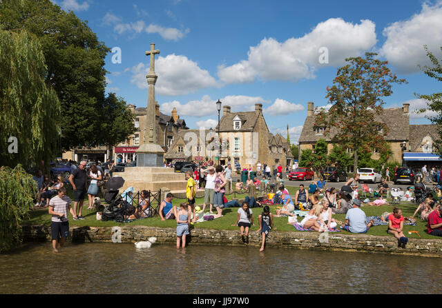 Crowd of people beside River Windrush on August bank holiday weekend, Bourton-on-the-Water, Cotswolds, Gloucestershire, - Stock Image