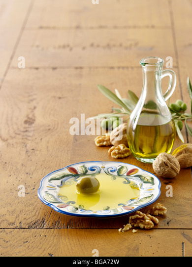 Olive oil and olive on plate with walnuts - Stock Image