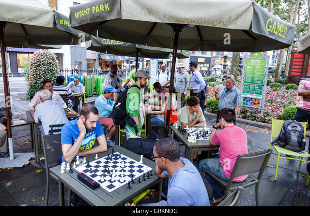 New York New York City NYC Manhattan Midtown Bryant Park public park games chess playing board Black man recreation - Stock Image