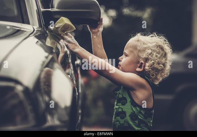 Boy washing car - Stock Image