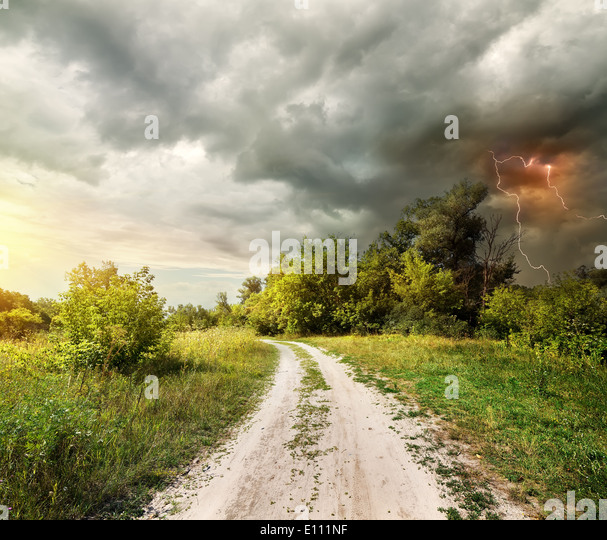 Country road through the forest and lightning - Stock-Bilder
