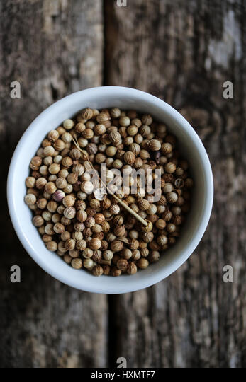 Coriander seeds in a white bowl on a wooden table - Stock Image