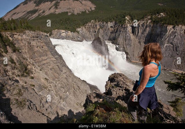 Woman enjoys view of Virginia Falls, Nahanni National Park Preserve, NWT, Canada. - Stock Image