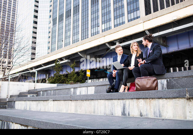 Low angle view of business people discussing while using laptop against building - Stock-Bilder