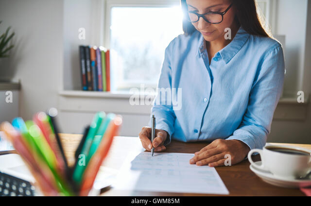 Young businesswoman busy writing notes or a report as she sits at her desk with window light coming in over her - Stock Image