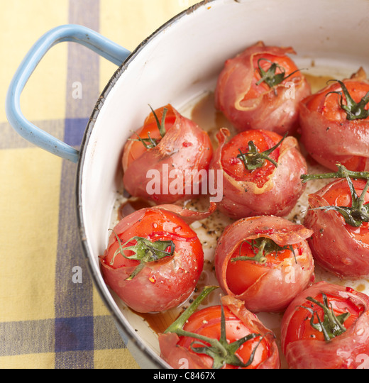 Pot of bacon wrapped tomatoes - Stock Image