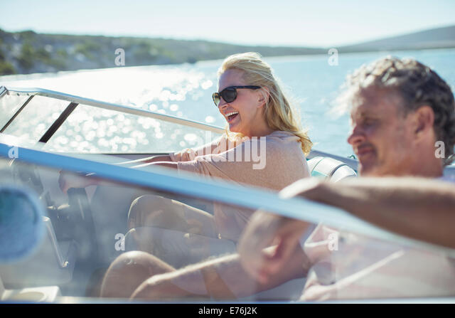 Couple driving boat in water - Stock-Bilder