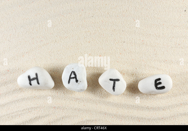 Hate word on group of stones with sand background - Stock Image