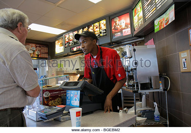 Georgia South Newport McDonald's Restaurant chain franchise dining fast food name brand counter Black man cashier - Stock Image