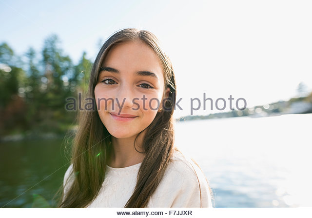 Portrait smiling brunette girl at lakeside - Stock-Bilder