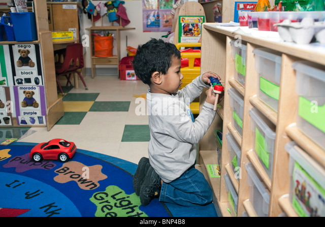preschool boy looking for a toy on shelve in the classroom - Stock Image