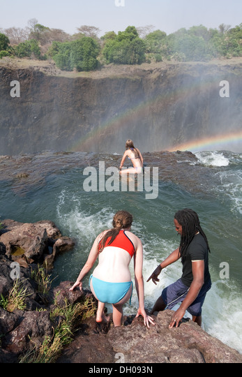 Tourists swimming in Devils Pool on the edge of the Victoria Falls, Zambia side, Africa - example of adventure travel - Stock-Bilder