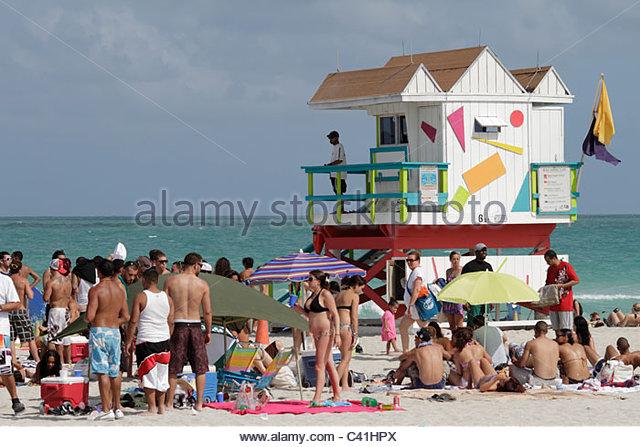 Miami Beach Florida Atlantic Ocean sunbathers weekend crowded packed Spring Break student lifeguard station - Stock Image
