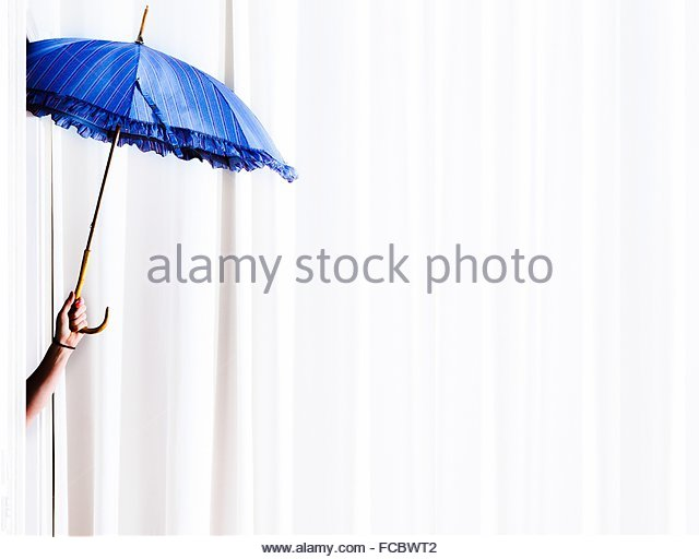 Cropped Image Of Woman Holding Blue Open Umbrella - Stock Image