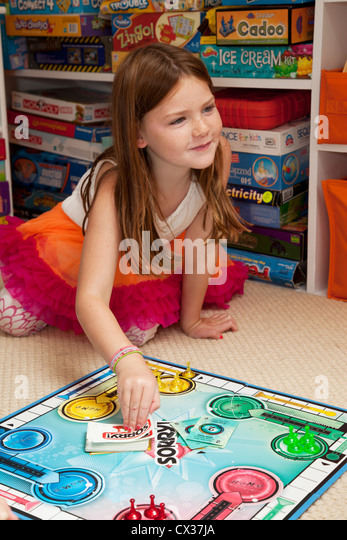 A little girl is playing a board game. - Stock Image