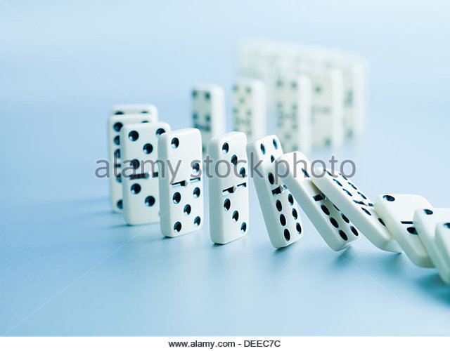 Dominoes falling in a row - Stock Image