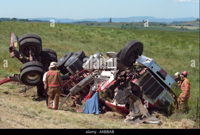 Fire fighters look at wreckage from a semi truck accident along highway 22 in Oregon USA - Stock Image