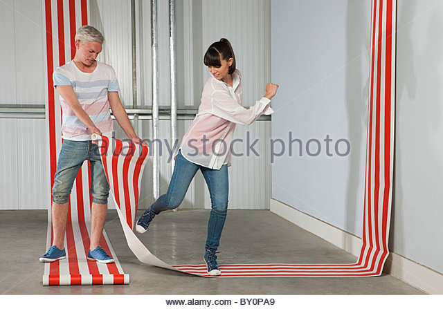 Young couple with striped wallpaper - Stock Image