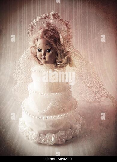 A vintage bridal doll head on top of a wedding cake. - Stock Image
