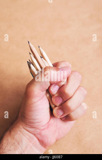 Male illustrator and sketch artist with handful of pencils, selective focus - Stock Image