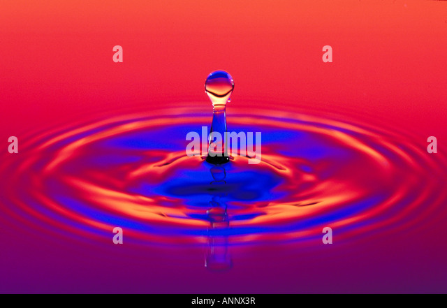 Pillar result of recoil from impact of water droplet Water frozen by strobe light. - Stock Image