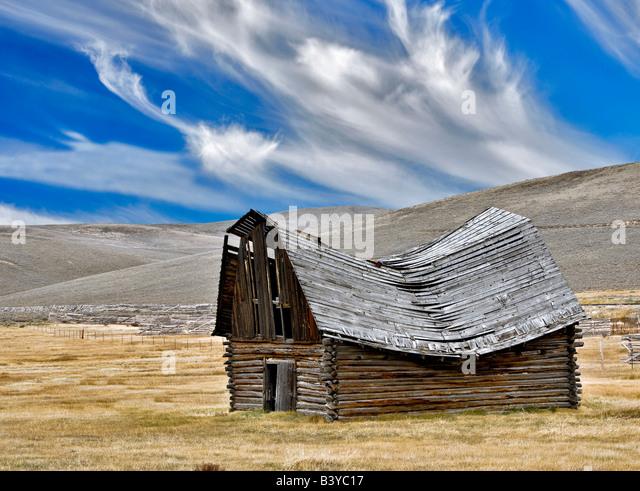 Fallen down barn with wispy clouds Montana - Stock-Bilder