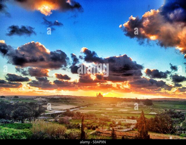 Xewkija church against setting sun with blue sky and clouds. - Stock Image