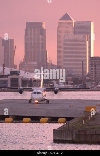 Turboprop regional airliner taxing at London City airport with Millenium Dome and Canary Wharf in the background - Stock Image