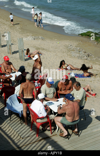Spain Barcelona beach Platja de la Barceloneta people old men playing cards - Stock Image
