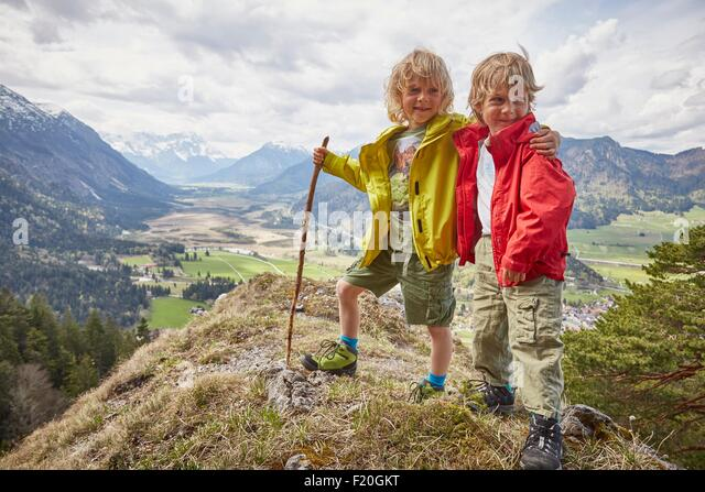 Portrait of two young boys, standing on hilltop, Garmisch-Partenkirchen, Bavaria, Germany - Stock Image
