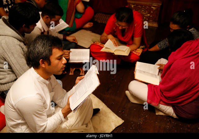 Gita Jayanti celebration in an ISKCON temple. Devotees reading the Bhagavad Gita. Sarcelles. France. - Stock Image