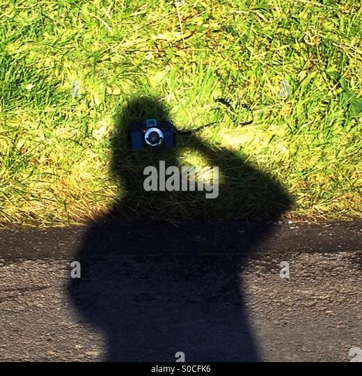Shadow taking a photo - Stock Image