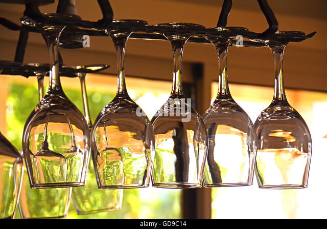 Glasses of wine hanging in a bar - Stock Image