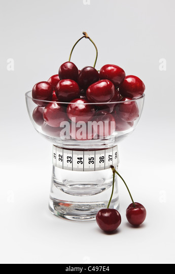 Cherries in Glass Dish with Tape Measure - Stock Image