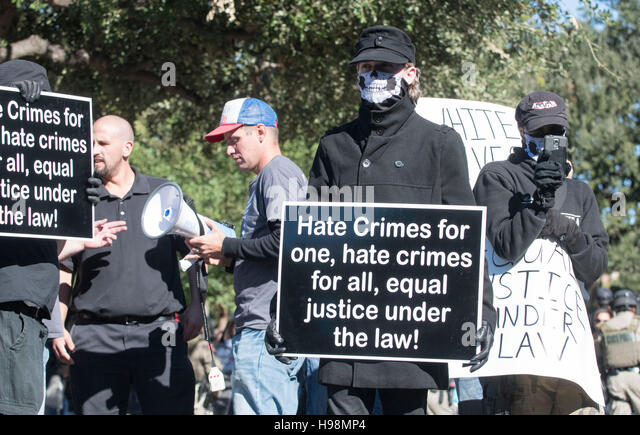 Masked white male marchers carry signs denigrating hate crime laws at White Lives Matter rally in downtown Austin - Stock Image