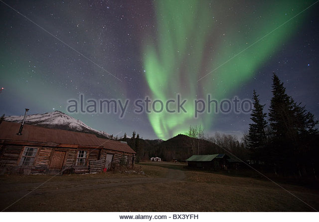 Aurora borealis shimmers over the Brooks Range and a historic cabin in Wiseman, Alaska during October 2009 - Stock-Bilder