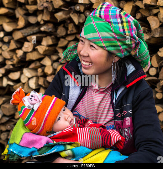 Happy Hmong woman with baby, smiling, sitting outside at Ta Van village near Sapa, Lao Cai Province, North Vietnam. - Stock-Bilder